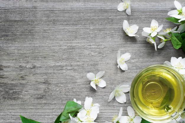Чашка зеленого чая жасмина и цветов жасмина на деревенском деревянном фоне