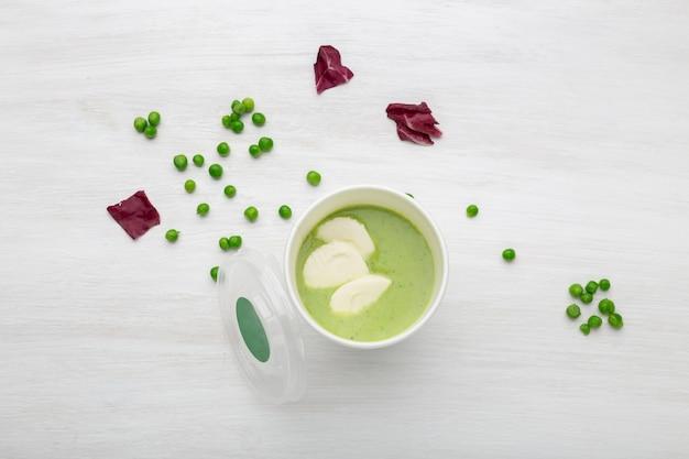 Чашка зеленого супа с кусочками овощей стоит на белом столе с зеленым горошком. концепция здорового питания.
