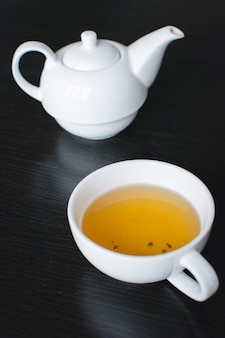 Cup of green tea and teapot