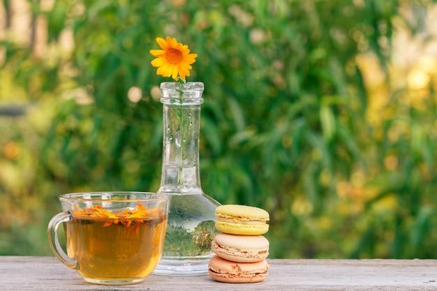 녹차 한 잔, 다양한 색상의 맛있는 마카롱 케이크와 금송화 꽃.