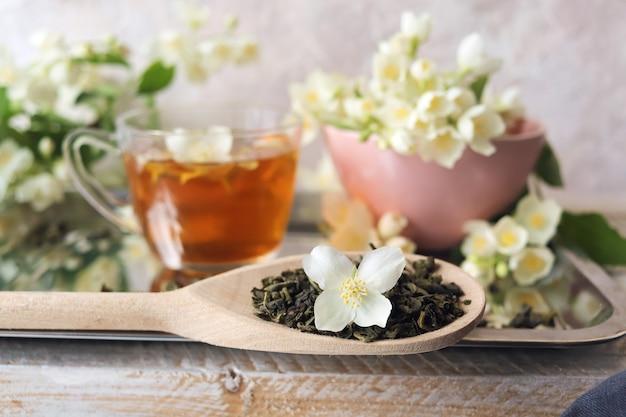 健康的な飲み物のテーブルの成分に緑茶ジャスミンの花のカップ