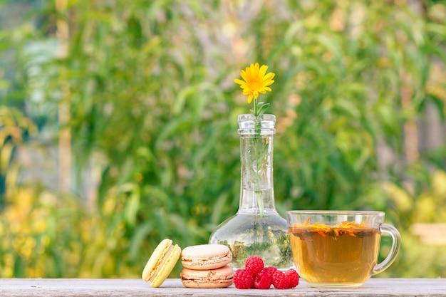 녹차 한 잔, 다양한 색상의 마카롱 케이크, 신선한 산딸기, 금송화 꽃.