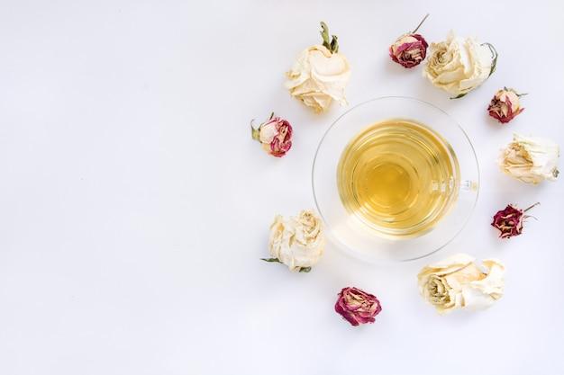 Чашка зеленого чая с сухими белыми розами вокруг.