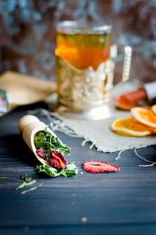 ミント、レモンスライス、ドライフルーツロール、イチゴとお茶のミントの葉と緑茶のカップ