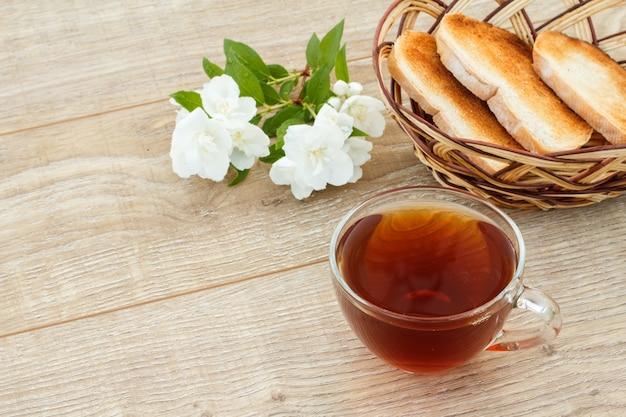 Чашка зеленого чая с белыми цветами жасмина, тосты в плетеной корзине на деревянных фоне. вид сверху.