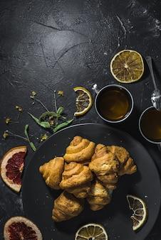 Чашка полезного лимонного чая с круассанами и цитрусовыми