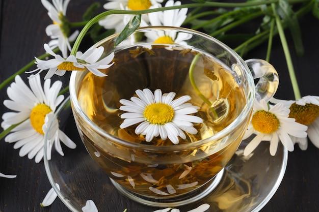 木製の背景に新鮮なデイジーの花とハーブカモミールティーのカップ。医師の治療と免疫の概念の予防
