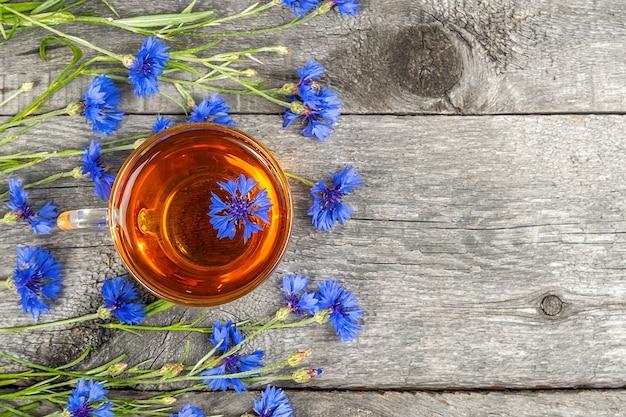 Чашка травяного чая и цветы синих васильков на деревянной поверхности