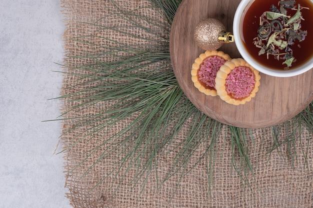 ハーブティー、クリスマスボール、木の板にクッキーのカップ。高品質の写真