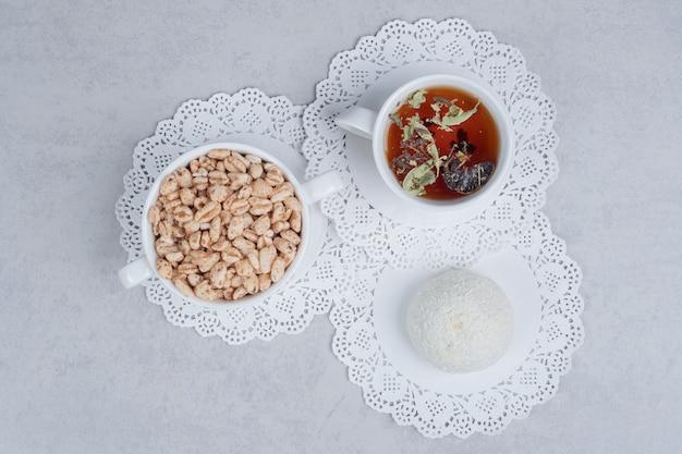 Чашка травяного чая, кокосовое печенье и миска конфет на белом столе. фото высокого качества
