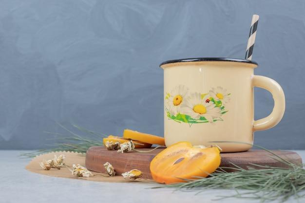 Чашка травяного чая, цветов и ломтиков хурмы на деревянной доске. фото высокого качества