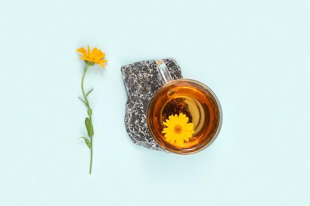 石の上のハーブティーと青い背景のキンセンカの花のカップ。心を落ち着かせる飲み物のコンセプト。