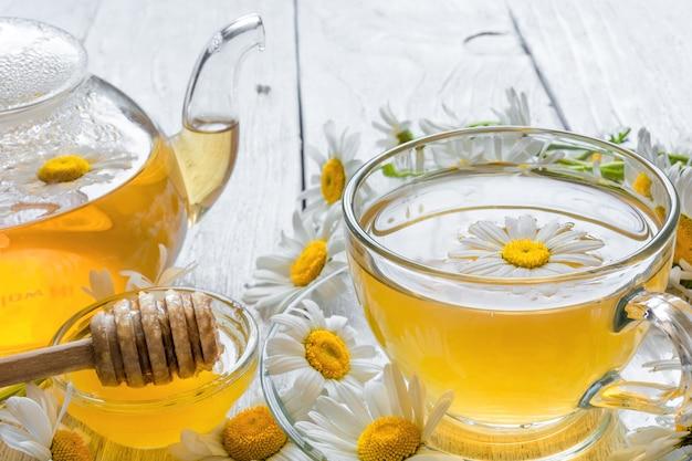 カモミールの花と蜂蜜とティーポットとハーブティーのカップ