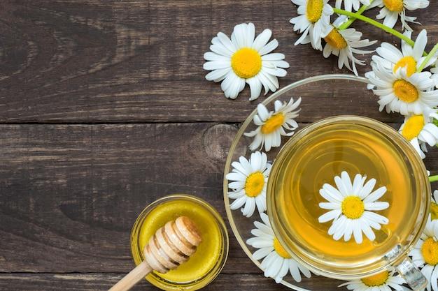 カモミールの花と蜂蜜とハーブティーのカップ