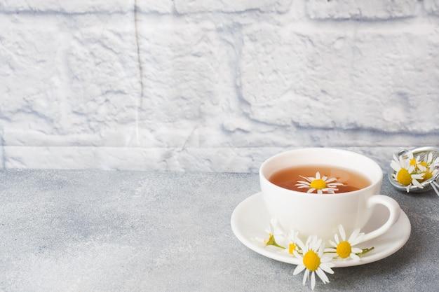 Чашка травяного чая с цветками ромашки на сером столе. копировать пространство