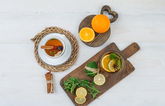 柑橘系の果物、まな板にミントの葉、白い表面にシナモンとハーブティーのカップ