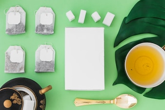 Cup of herbal tea with different types of tea bag and sugar cubes on green background