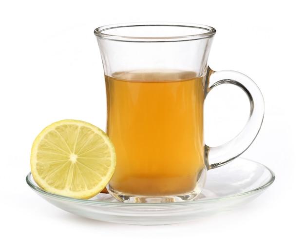 흰색 배경 위에 레몬을 넣은 허브 차 한잔
