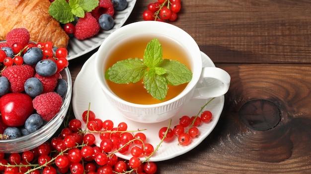 디저트와 크루아상을 배경으로 그릇에 민트 잎 열매를 넣은 허브 차 한 잔