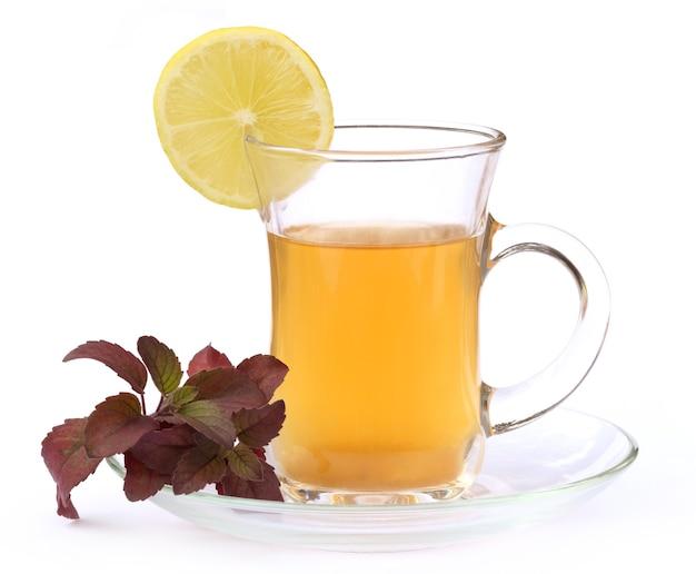 흰색 배경에 붉은 털시 잎과 레몬을 넣은 허브차 한 잔