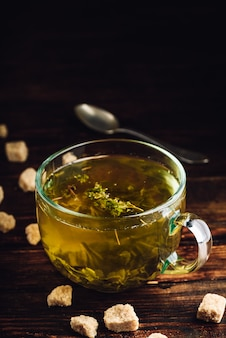 Чашка травяного чая с рафинированным сахаром на деревянном фоне