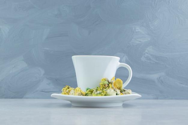 黄色い花とハーブティーのカップ。