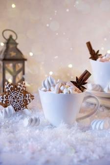 Чашка горячего напитка с зефиром и специями на снегу.
