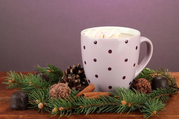 Чашка горячего какао с конфетами и еловыми ветками на столе на темном фоне