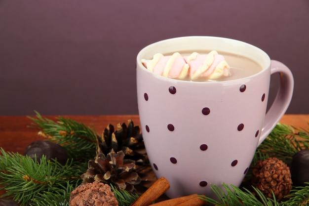 Чашка горячего какао с конфетами и еловыми ветками на столе