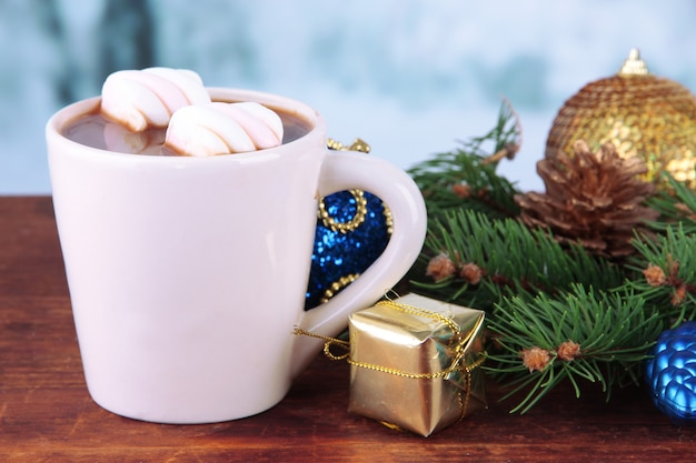 Чашка горячего какао с рождественскими украшениями на столе на яркой поверхности