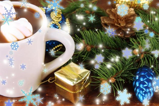 木製の背景にクリスマスの装飾とホットカカオのカップ