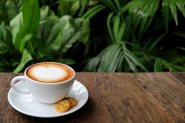 ぼやけた緑の葉が付いている木のテーブルで役立ったクッキーとホットカプチーノコーヒーのカップ