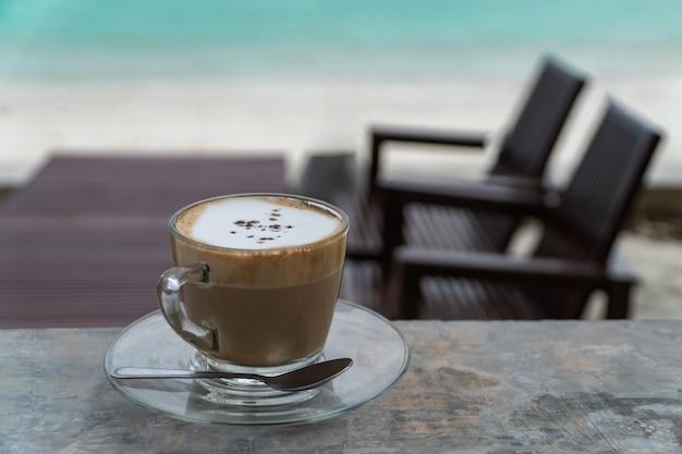 テラスの熱いカプチーノと海のビーチのぼやけた机のカップ。