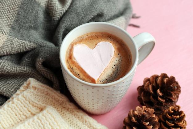 Чашка горячего капучино с зефиром и теплой одеждой на розовом фоне, крупным планом