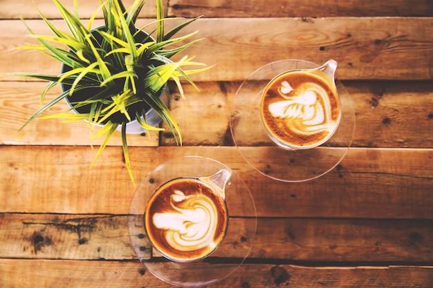 뜨거운 카푸치노 한 잔이 나무 테이블에 있습니다. 아침 시간.