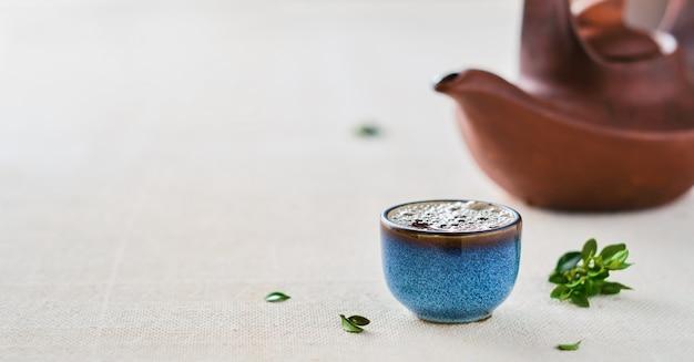 熱い中国の緑茶のカップ。テーブルの上のティーポットと緑の葉。カップにセレクティブフォーカス。コピースペースのあるクローズアップ。お茶会のアイデア、ミニマリズム。