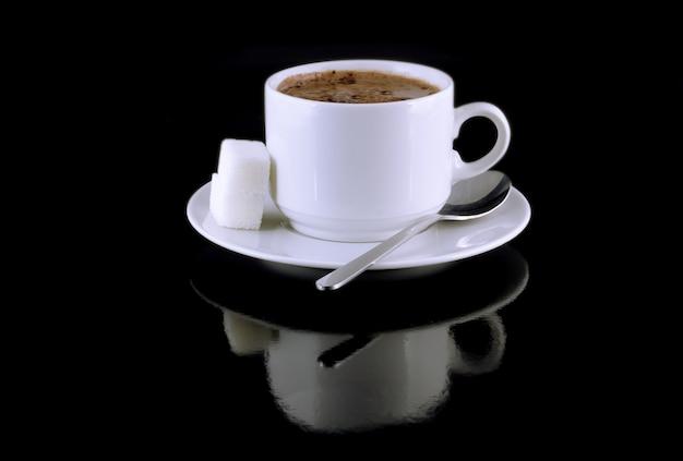黒の背景にホットチョコレート、砂糖のカップ。