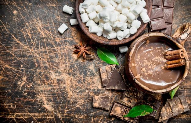 素朴なテーブルにシナモンスティックとマシュマロとホットチョコレートのカップ。