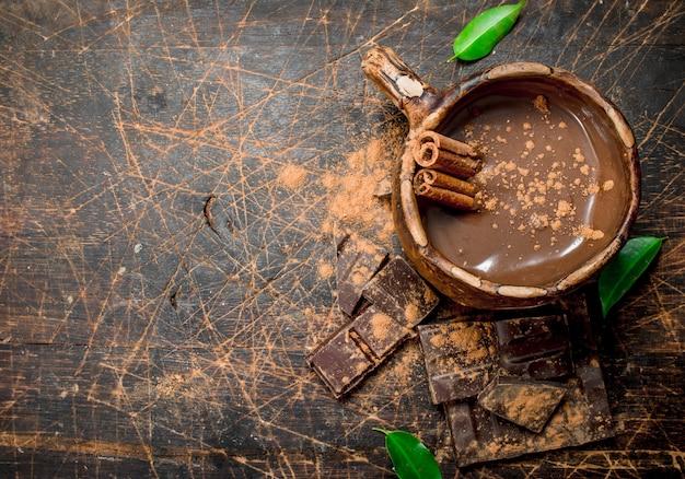 Чашка горячего шоколада с палочками корицы на деревенском столе.