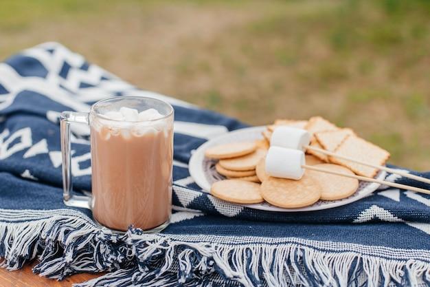 スモアが作ったスティックで揚げるためのマシュマロクッキーとマシュマロが入ったホットチョコレートのカップ
