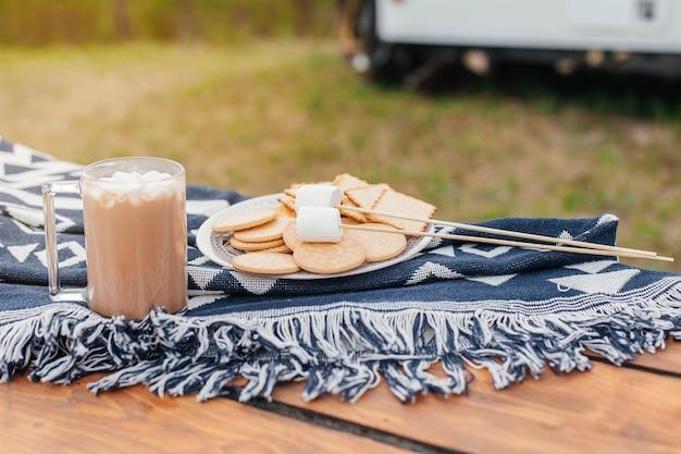 スティックで揚げるためのマシュマロクッキーとマシュマロとホットチョコレートのカップ