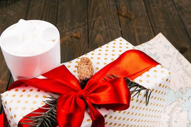 Чашка горячего шоколада с зефиром стоит перед красной настоящей коробкой на белой карте
