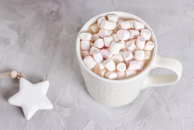 Чашка горячего какао и зефира, серая поверхность