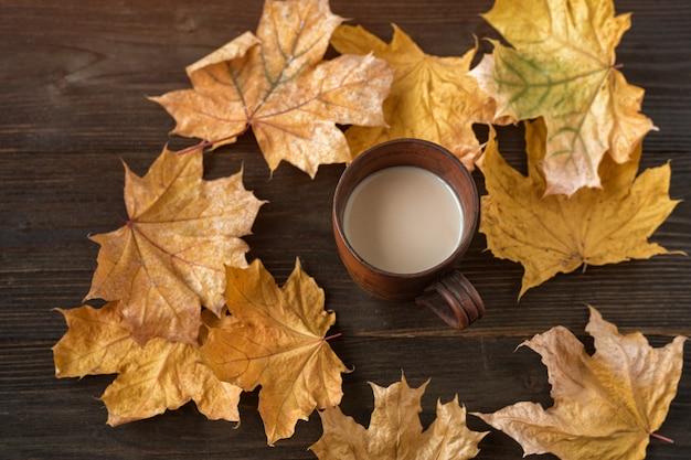 Чашка горячего какао на деревянных фоне среди осенних листьев. кофе с молоком и осенними листьями.
