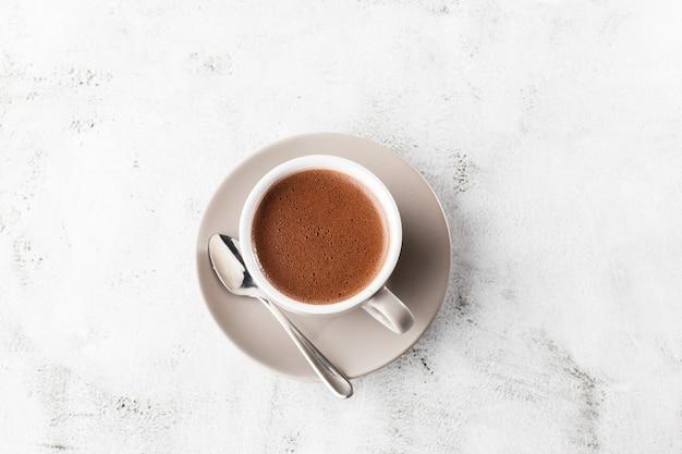 ホットココアやホットチョコレートや明るい大理石の背景に分離された白いカップでアメリカーノのカップ。俯瞰、コピースペース。カフェメニューの宣伝。コーヒーショップメニュー。縦の写真。伝統的な
