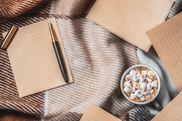 ウールの格子縞の背景にマシュマロ、空白のページとインクペンとホットココアのカップ