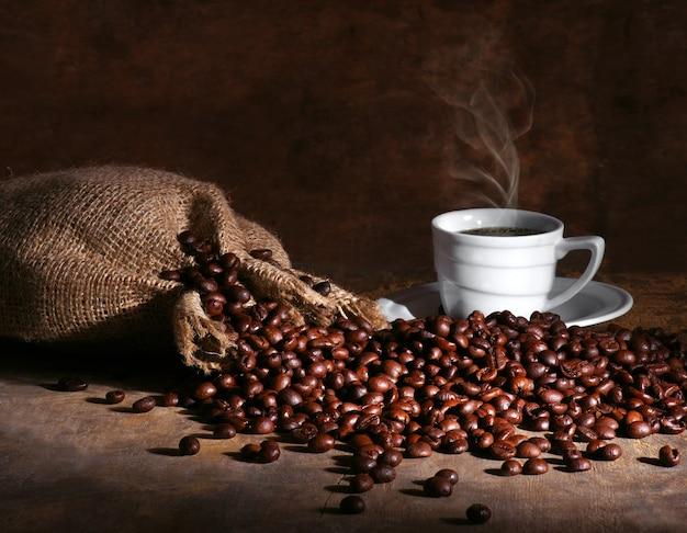 Чашка горячего кофе и зерен на темном фоне