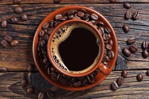 어두운 나무 테이블에 뜨거운 커피와 콩 한 잔, 위쪽 전망