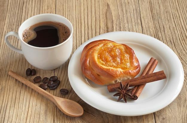 一杯のホットコーヒーと木製のテーブルにジャムとパン