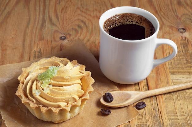 오래된 나무 테이블에 크림과 마멀레이드를 넣은 뜨거운 커피와 케이크 한 잔